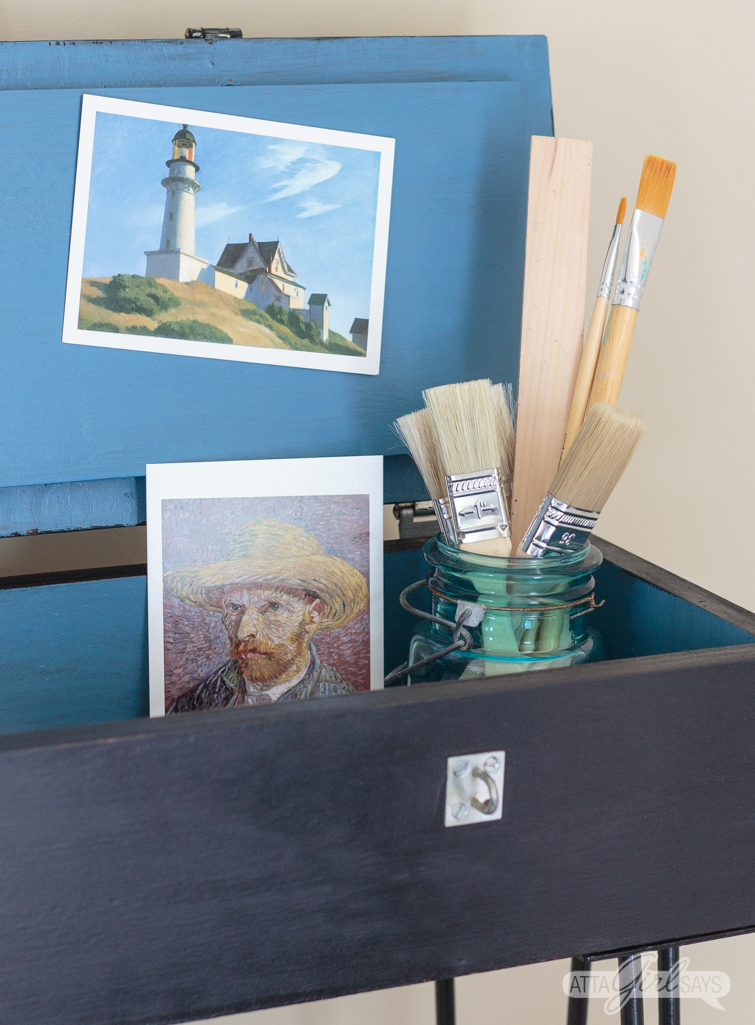 Interior hairpin leg storage compartment, painted blue in contrast to the black exterior. The desk is filled with art postcards and envelopes.