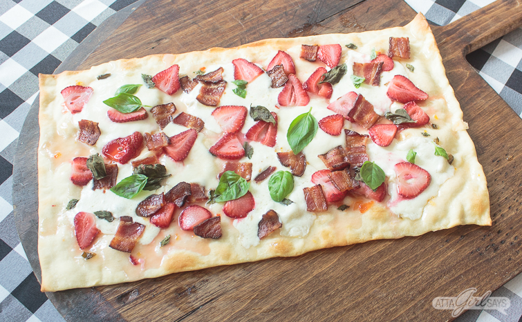 Strawberry bacon flatbread pizza with basil on a wooden pizza peel on top of a black and white gingham tablecloth