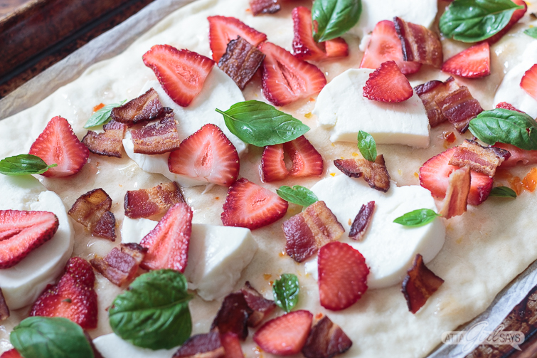 closeup of a flatbread pizza with strawberries, bacon, basil and fresh mozzarella