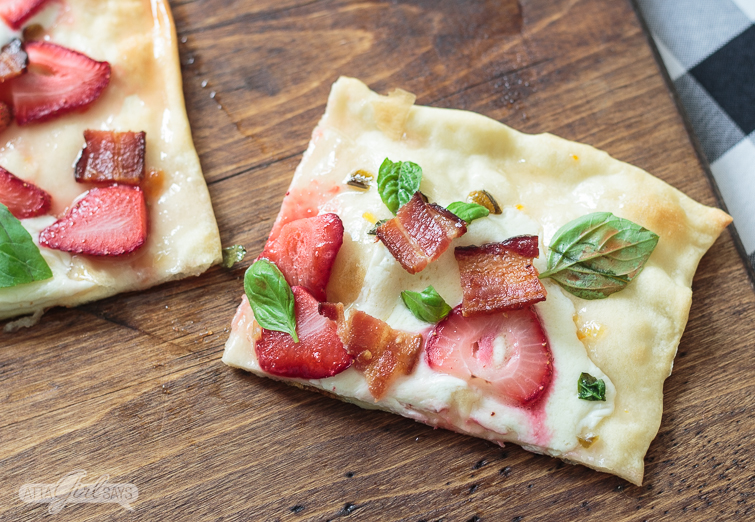 overhead photo of a slice of strawberry bacon flatbread pizza recipe on a wooden pizza peel