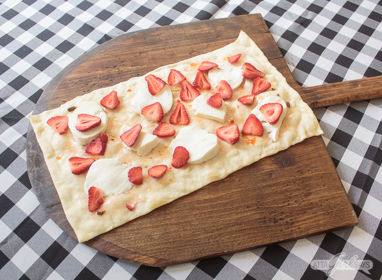 rectangular flatbread pizza crust, topped with strawberries, pepper jelly and fresh mozzarella, on a wooden pizza peel on top of a gingham check tablecloth