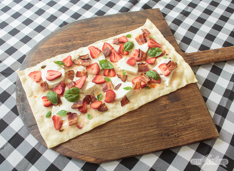 rectangular flatbread pizza crust, topped with pepper jelly, fresh mozzarella, strawberries, basil and bacon on a wooden pizza peel on top of a gingham check tablecloth