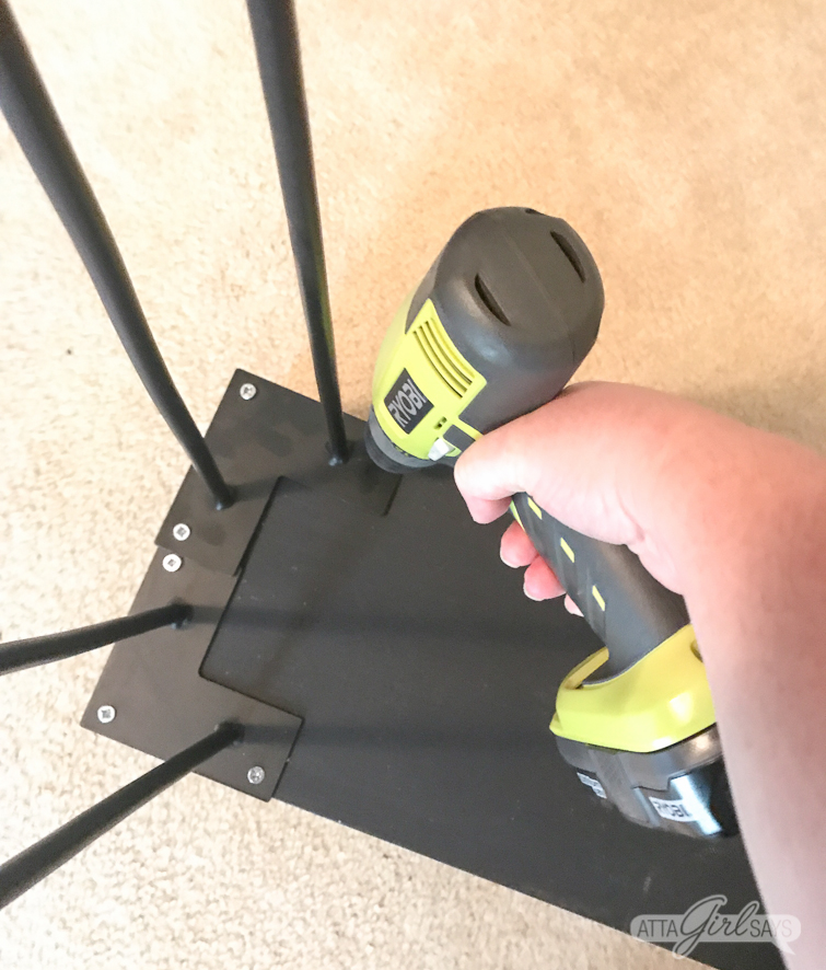 Underside of DIY hairpin leg desk. Photo shows someone using a drill to attach hairpin legs to the bottom of a desk.