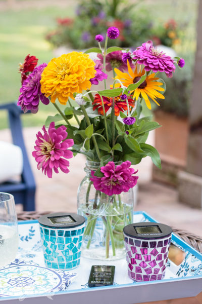 bouquet of flowers on a pretty melamine tray with two solar tealight candles in an outdoor setting for an article about outdoor entertaining ideas