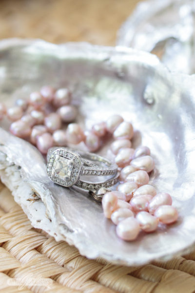 Photo of a platinum Asccher cut diamond engagement ring and wedding band and a pink freshwater pearl bracelet on a silver oyster shell jewelry dish