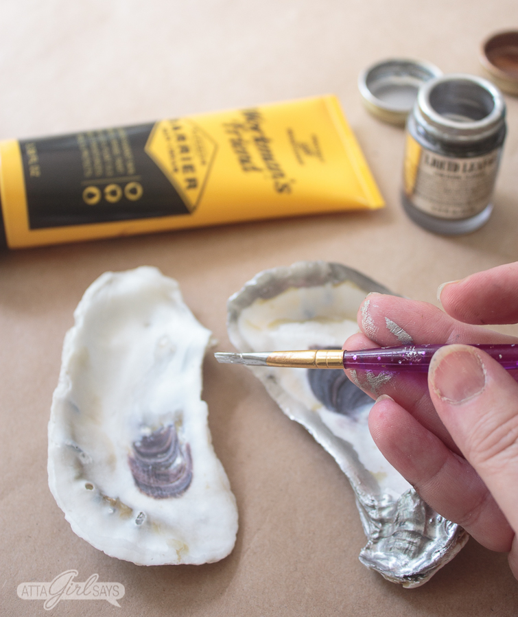 woman's hand holding a paintbrush and painting silver liquid leaf on a pair of large oyster shells.