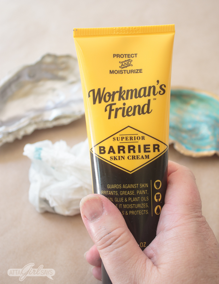 Woman's hand holding a tube of Workman's Friend Barrier Skin Cream with a paper towel and two painted oyster shells sitting on Kraft paper in the background
