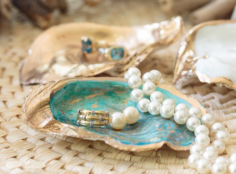 A gold diamond stacked ring sits on a green and gold oyster shell jewelry dish alongside a pair of pearl earrings and a pearl necklace. A gold oyster shell jewelry dish is shown in the background with two blue topaz rings sitting on it.