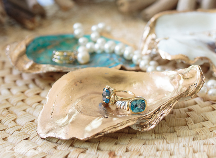 An antique emerald cut blue topaz ring, set in gold, sits on a gilded oyster shell craft jewelry dish alongside a silver and gold topaz Charles Krypell ivy blue topaz ring.