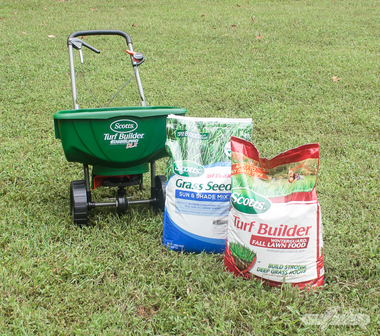 bags of grass seed and fertilizer on a lawn beside a Scotts broadcast seed spreader