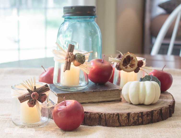 fall centerpiece with crabapples, fall squash, old books, tealight candle holders and blue mason jars, a wood slice and a burlap tablecloth