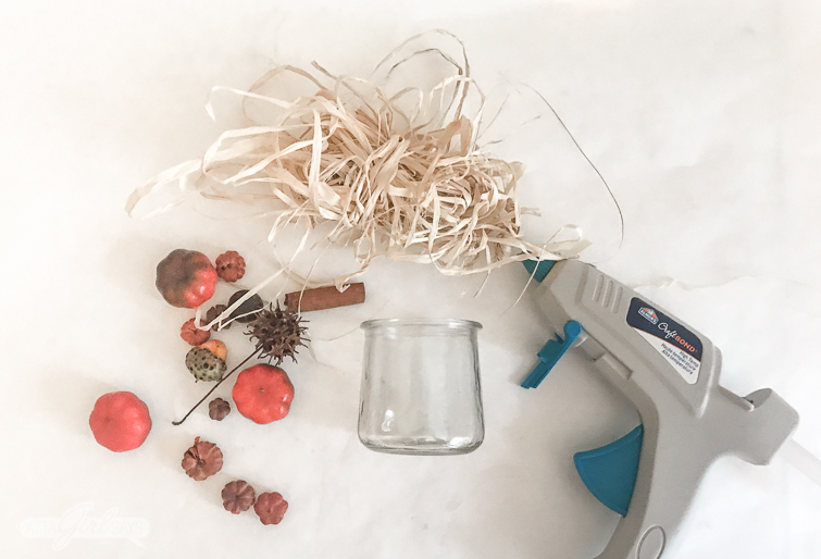 overhead photo with a hot glue gun, glass yogurt jar, raffia and miniature pumpkins, acorns and seed pods on a white background