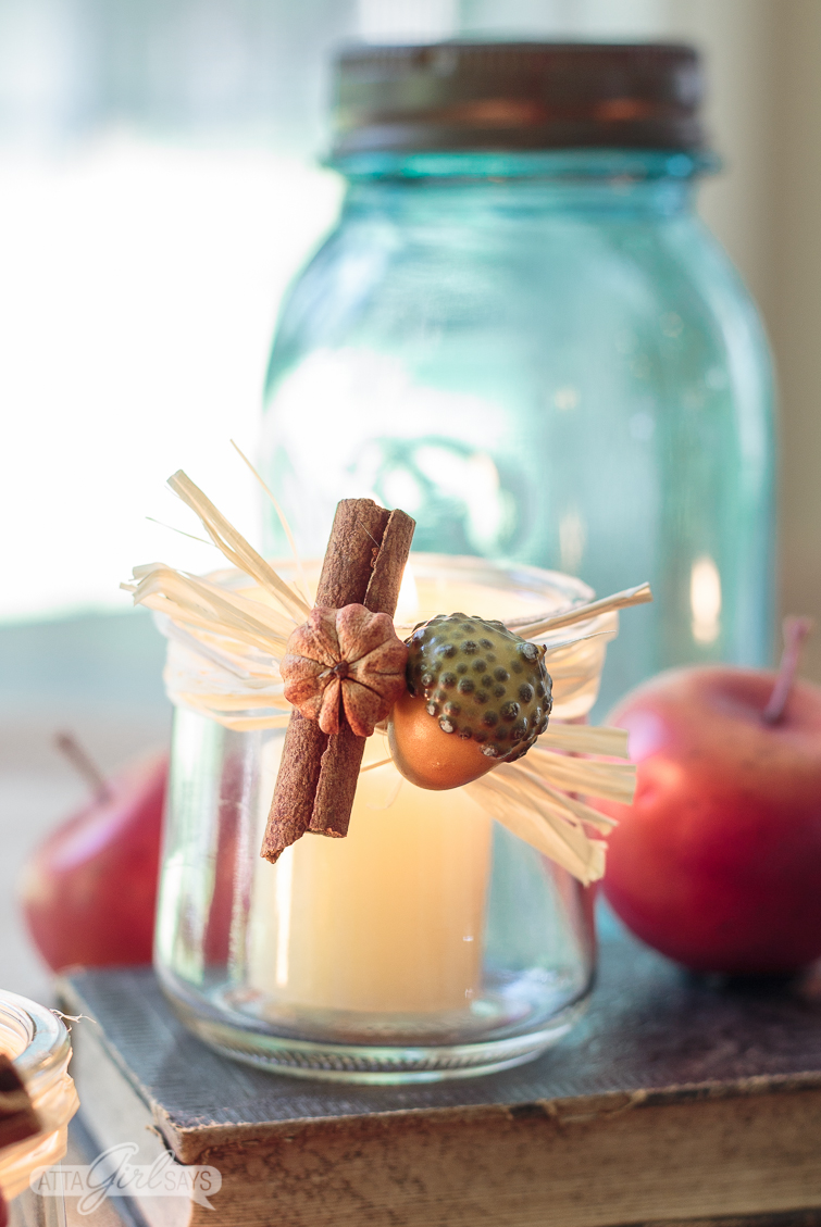 closeup of a glass yogurt jar candleholder decorated with miniature seed pods, acorn, raffia and a cinnamon stick. The votive is sitting on an old book with a blue glass mason jar and crabapples in the background