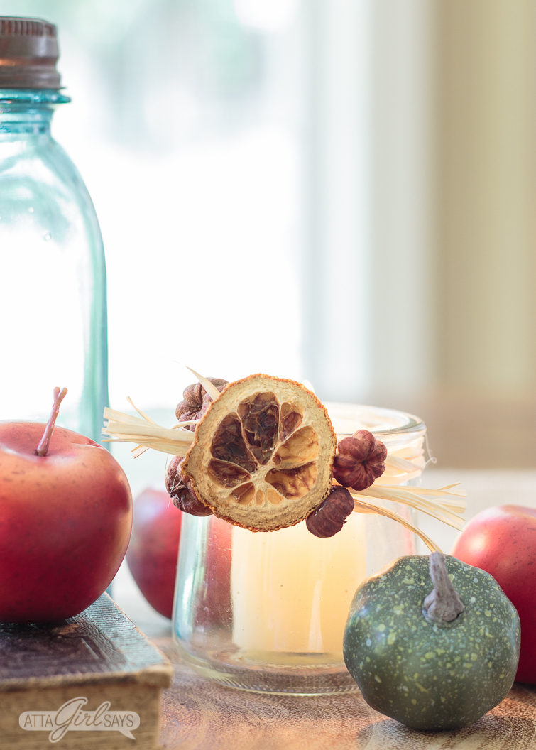 glass votive candle holder decorated with a dried orange slice, raffia and seed pods. A blue glass mason jar, crabapples and small squash are in the foreground
