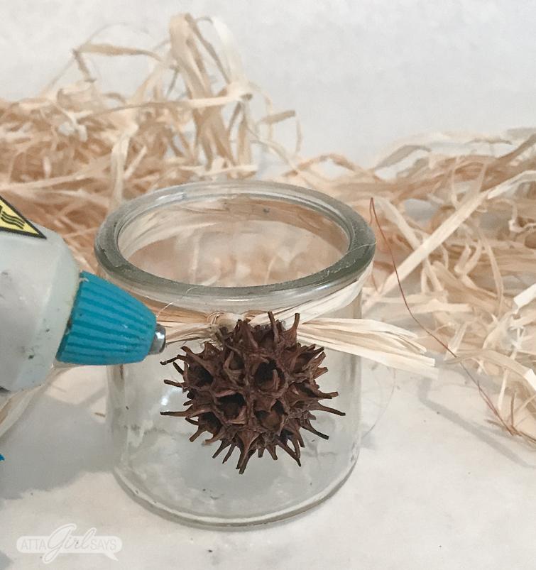 a hot glue gun gluing a sweet gun ball to the neck of a glass yogurt jar