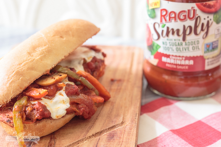 hot italian sausage and peppers sandwich on a wooden cutting board atop a red-and-white checked tablecloth with a jar of RAGU pasta sauce in the background.