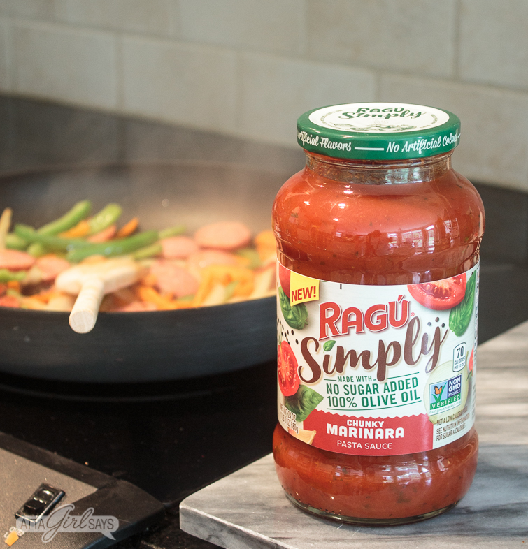 New RAGÚ® Simply Chunky Marinara Pasta Sauce on a marble cutting board beside a stovetop with a pan of smoked sausage and vegetables in the background
