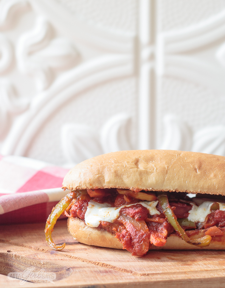 hot Italian sausage and peppers sub sandwich, loaded with vegetables and marinara sauce, sitting on a wooden cutting board