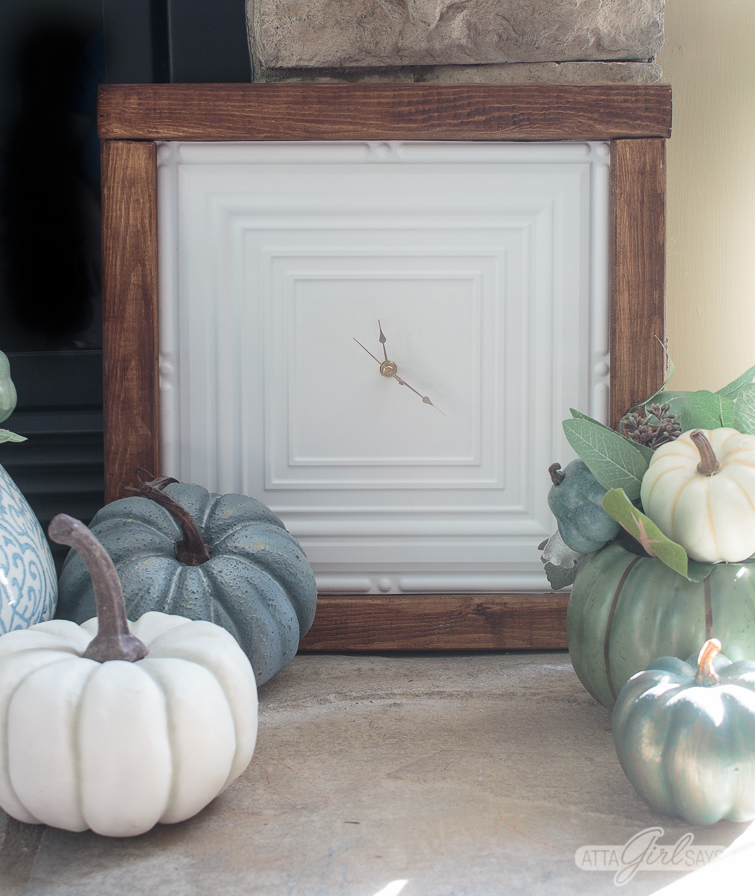 clock made from a white faux tin ceiling tile framed in a simple stained wood frame