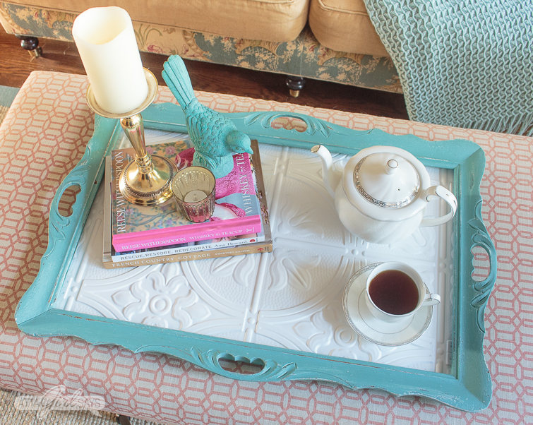 overhead shot of a tray made from an old frame and faux tin ceiling tiles. The tray is painted aqua blue and has a teapot, coffee pot and a stack of books on it, along with a two candles and a bird figurine