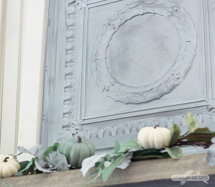 closeup of a silver tin ceiling panel on a fireplace mantel, decorated with a silvery green fall garland