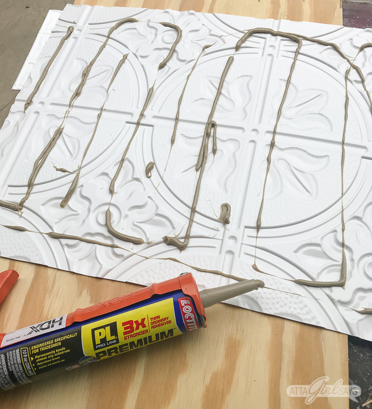 adding Loctite Premium adhesive to the back of a faux tin ceiling tile