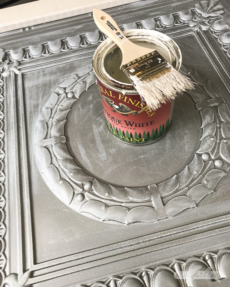paint can and paint brush sitting on top of a silver faux tin ceiling tile