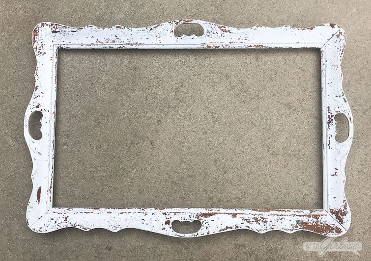 empty, chippy white wooden frame sitting on a paved driveway