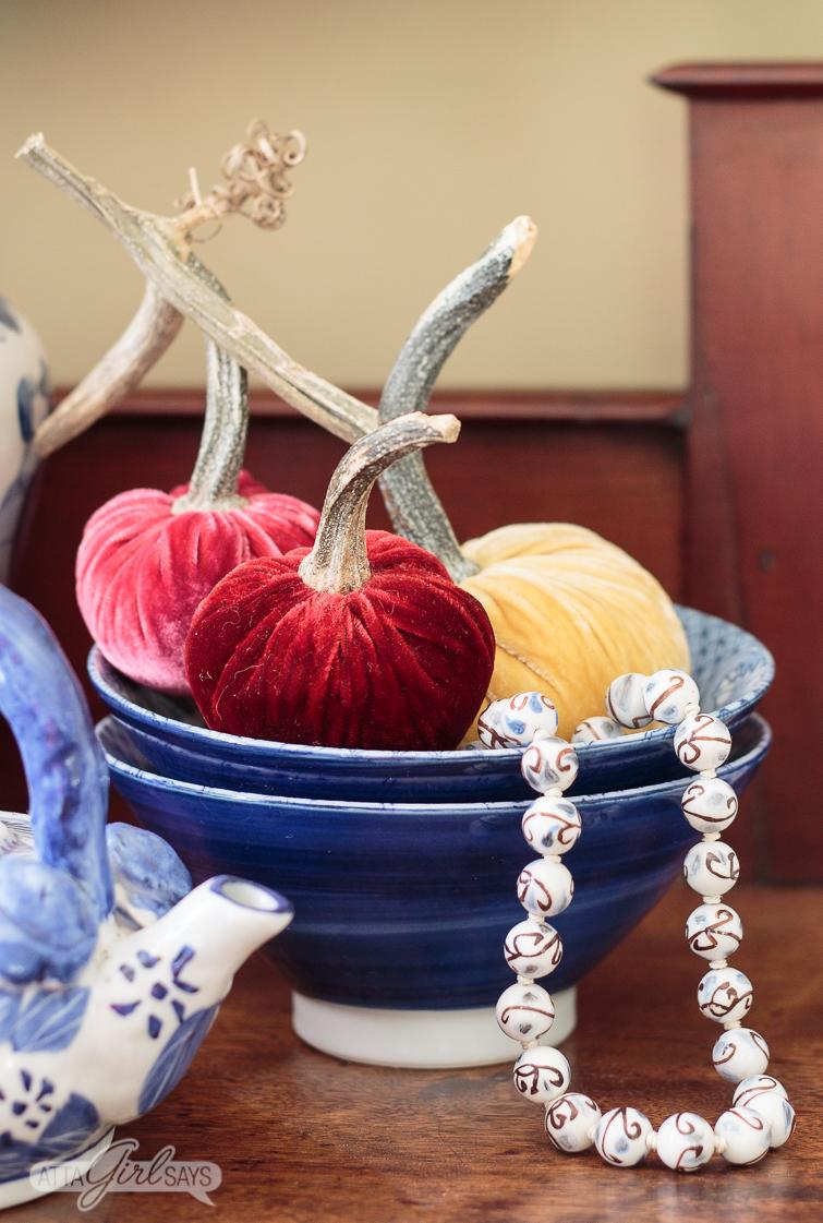 burgundy, mauve and gold velvet pumpkins in a blue bowl