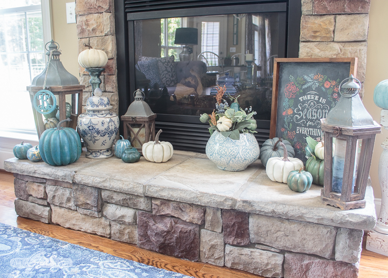 stone fireplace heart decorated for fall with chalkboard art, blue and white ginger jars and pottery and blue, white and aqua pumpkins