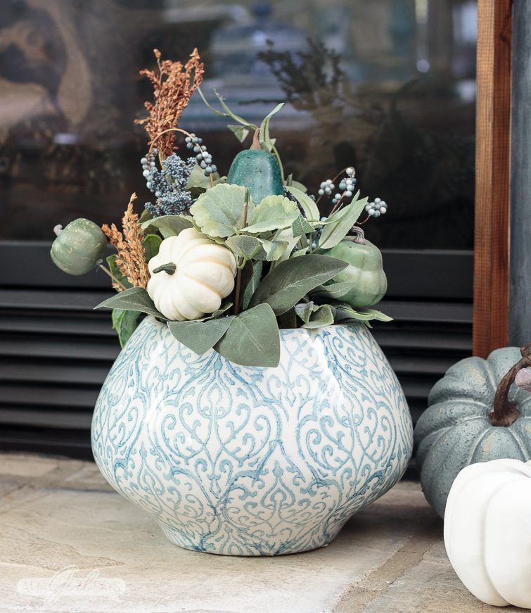 blue and white ginger jar vase filled with a fall floral arrangement with miniature white pumpkins