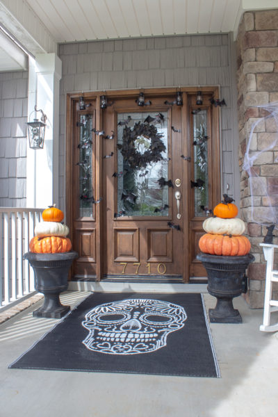 black skeleton rug and two Cinderella pumpkin topiaries in black urns on a Halloween front porch