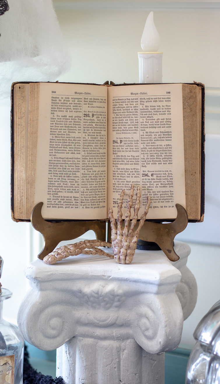 German book on a brass stand atop a plaster column with skeleton hand