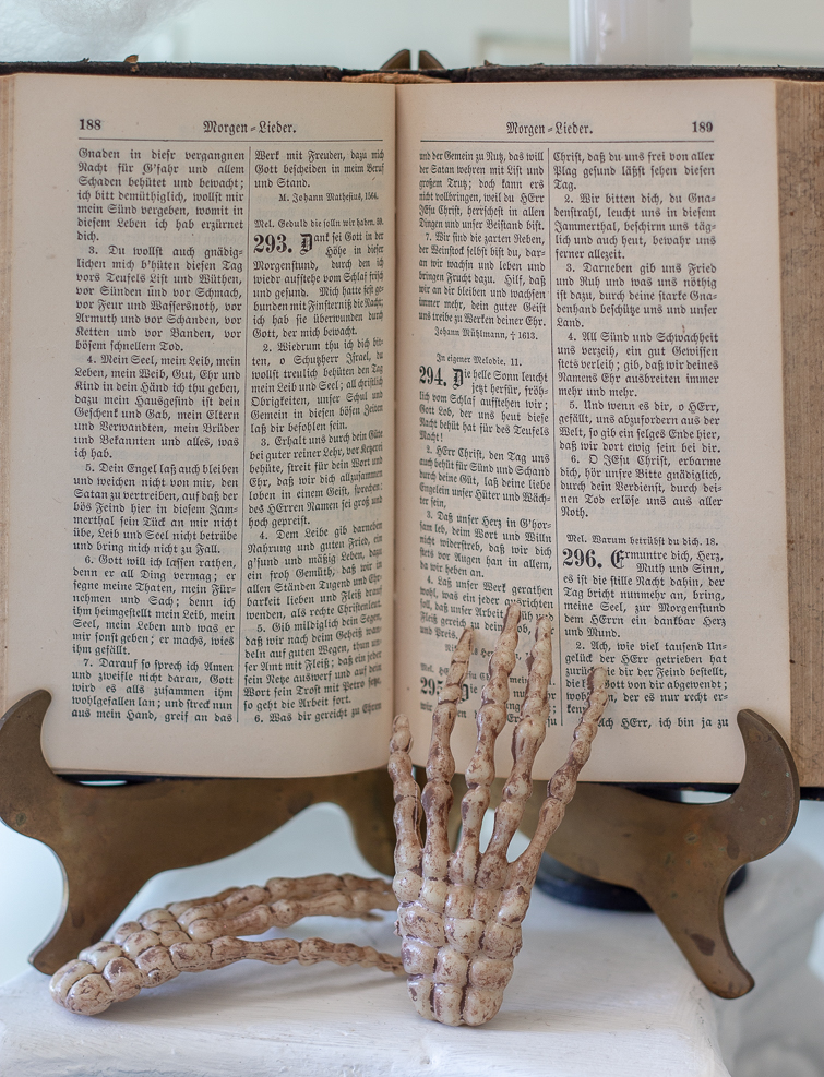 German book on a brass stand with skeleton hand