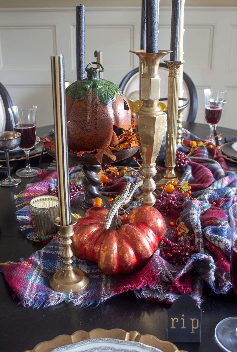antique brass candlesticks on a fall harvest Halloween dining table with orange metallic pumpkins and a plaid blanket scarf tablecloth