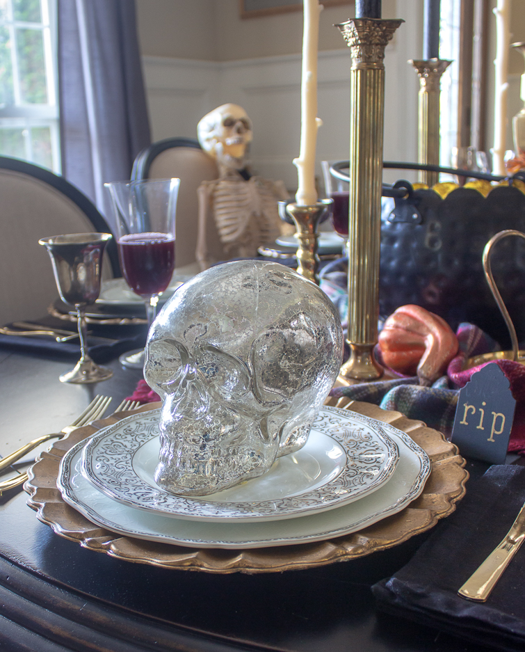 silver mercury glass skull on silver and white china as part of Halloween table decorations