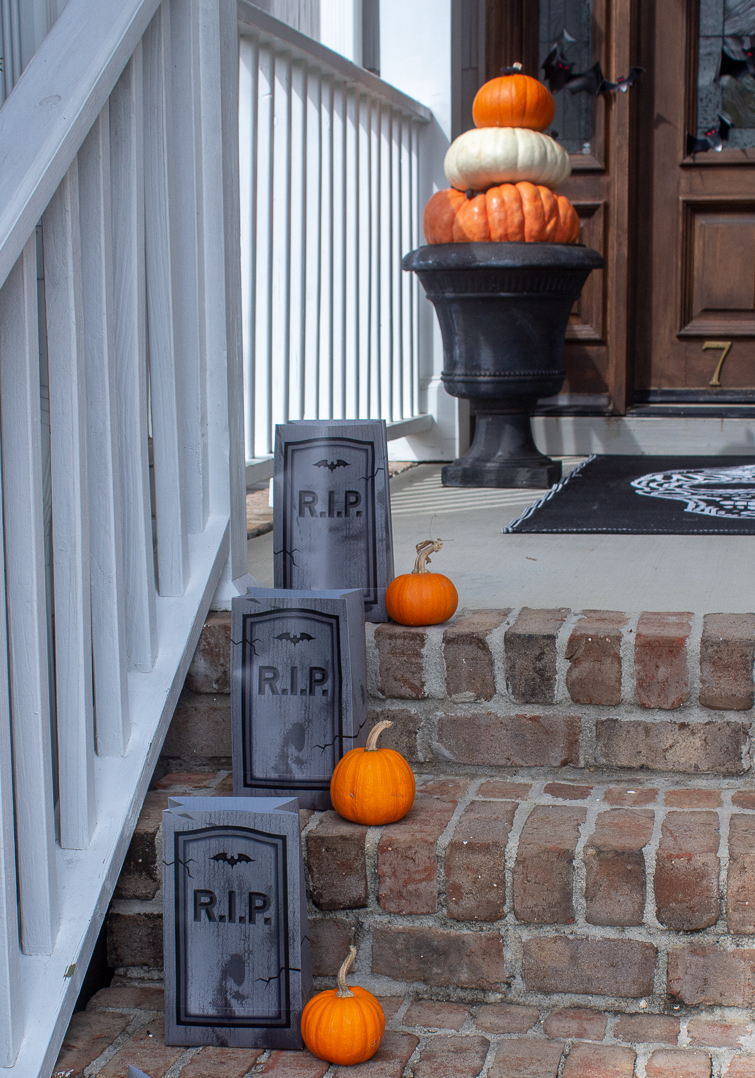 tombstone Halloween luminarias with mini pumpkins on brick porch steps