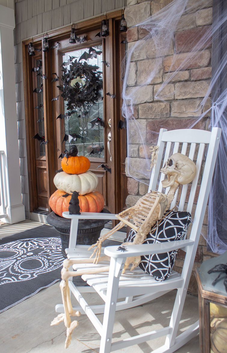 Halloween porch with a skeleton in a rocking chair with a Cinderella pumpkin topiary in a black urn in the foreground