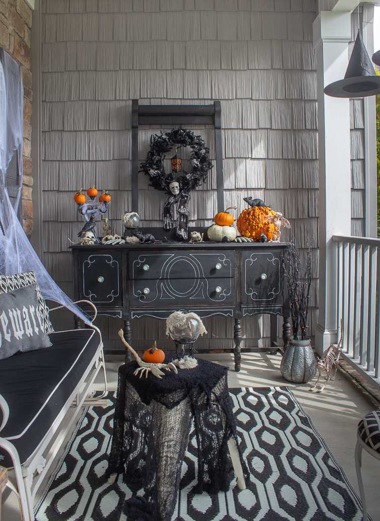 Halloween front porch decorations with a skeleton in a rocking chair and a black buffet decorated with black, white and orange spooky items