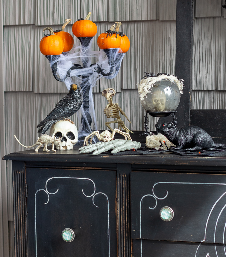 candleabara with pumpkins, spider webs, crystal ball, skulls, animal skeletons and rats sitting on a black buffet