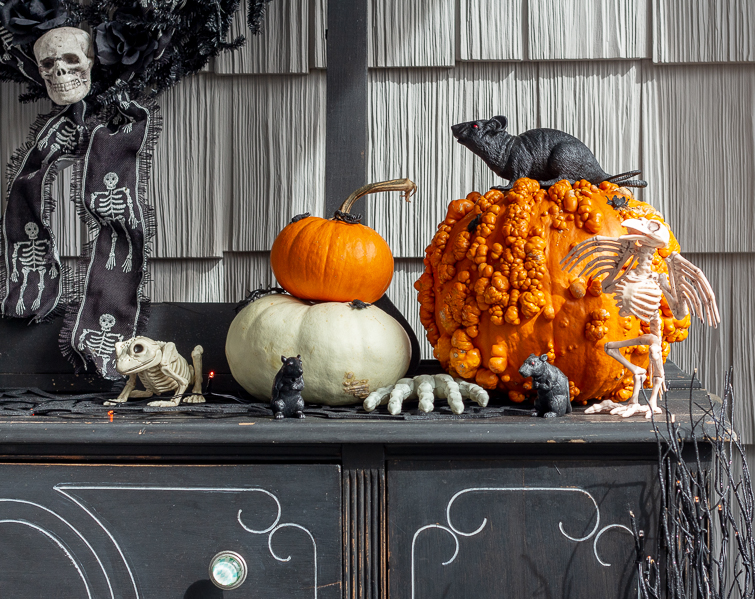 orange and white pumpkins on a black bufffet with plastic rats, animal skeletons and skeleton hands