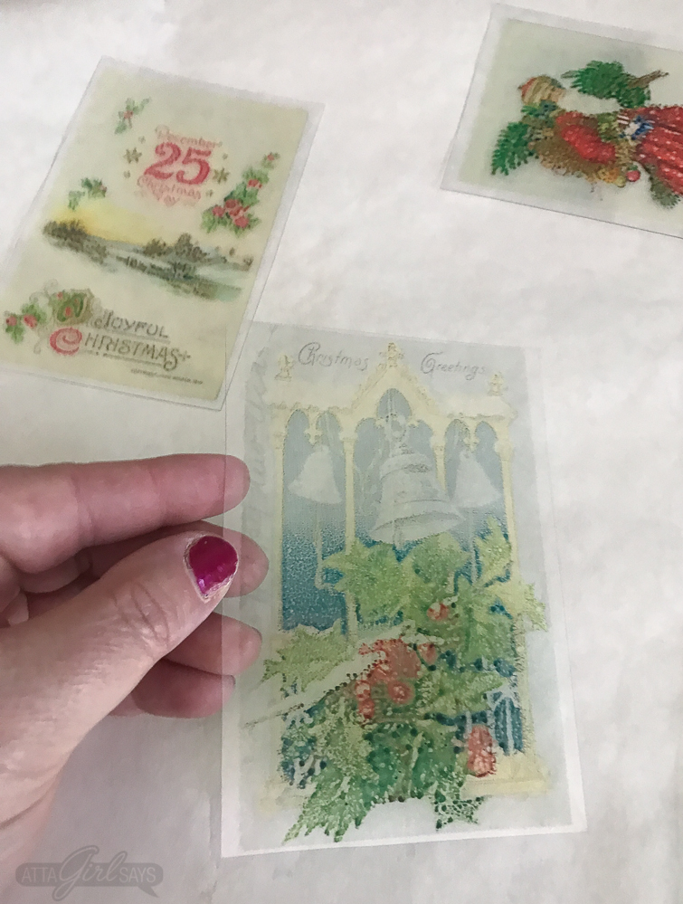 woman's hand holding a clear piece of Shrinky Dinks paper printed with a Christmas window scene from a vintage holiday postcard
