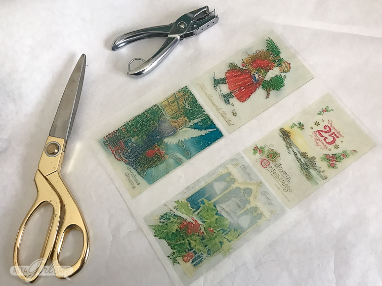 clear sheet of Shrinky Dinks paper with vintage postcard images printed on it on a desktop beside gold scissors and a hole punch