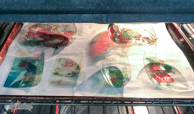 Vintage Christmas postcard Shrinky Dinks Christmas ornaments curling up in the oven on a parchment lined baking sheet