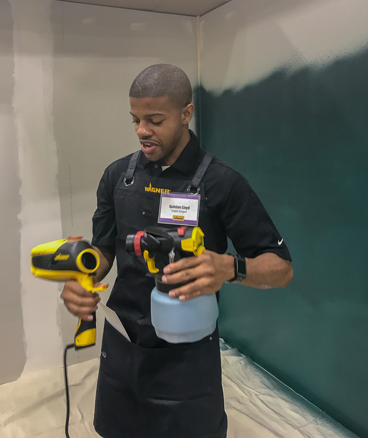 man holding a paint sprayer in a half-painted room
