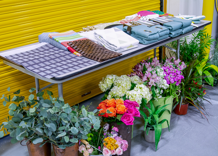 linens and fresh flowers set up on a table and the floor in a warehouse