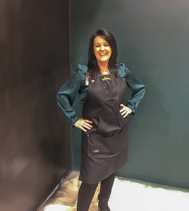 woman in a green shirt and black pants with a black apron standing in a room with a black and green wall