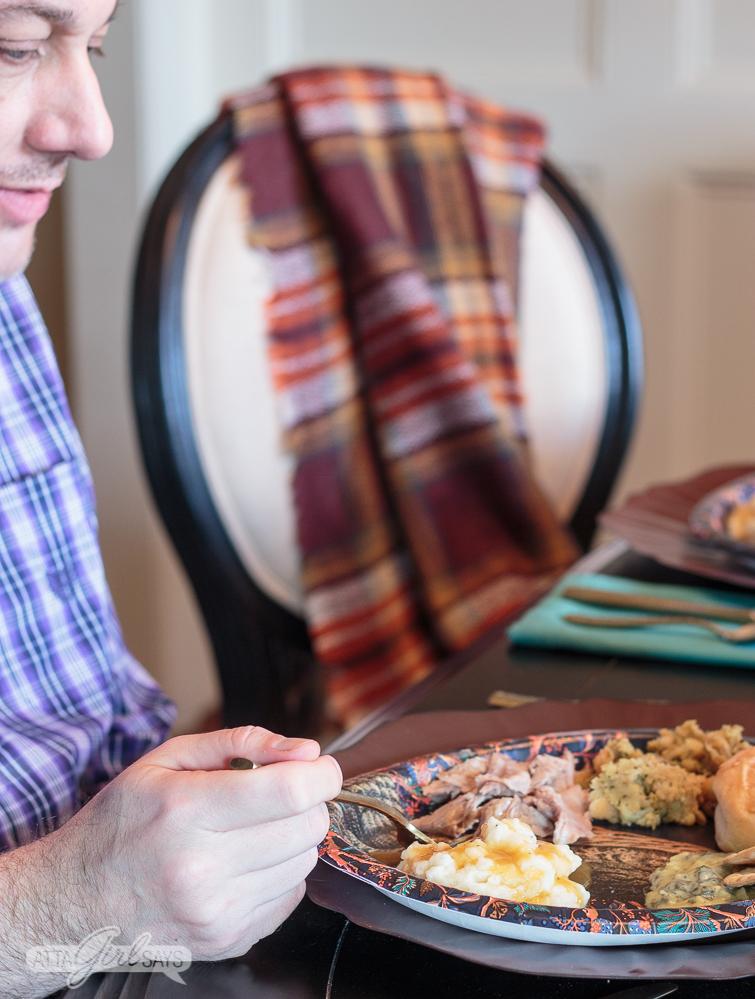man in a purple plaid shirt eating Thanksgiving dinner