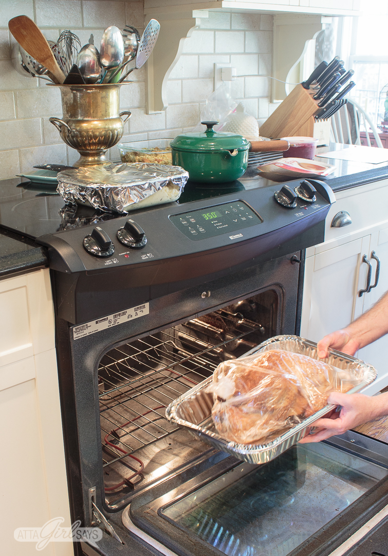 man putting a Thanksgiving turkey into an oven