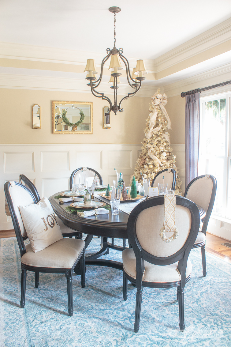 formal dining room decorated for Christmas with a gold tree and Christmas table decorations